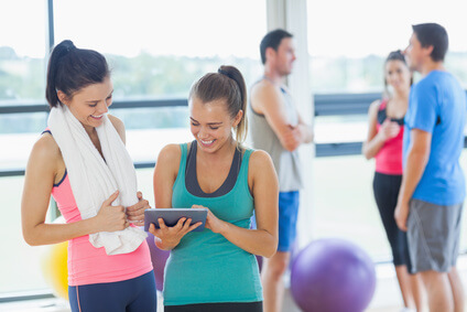 Fit women looking at digital table with friends chatting in background in bright exercise room