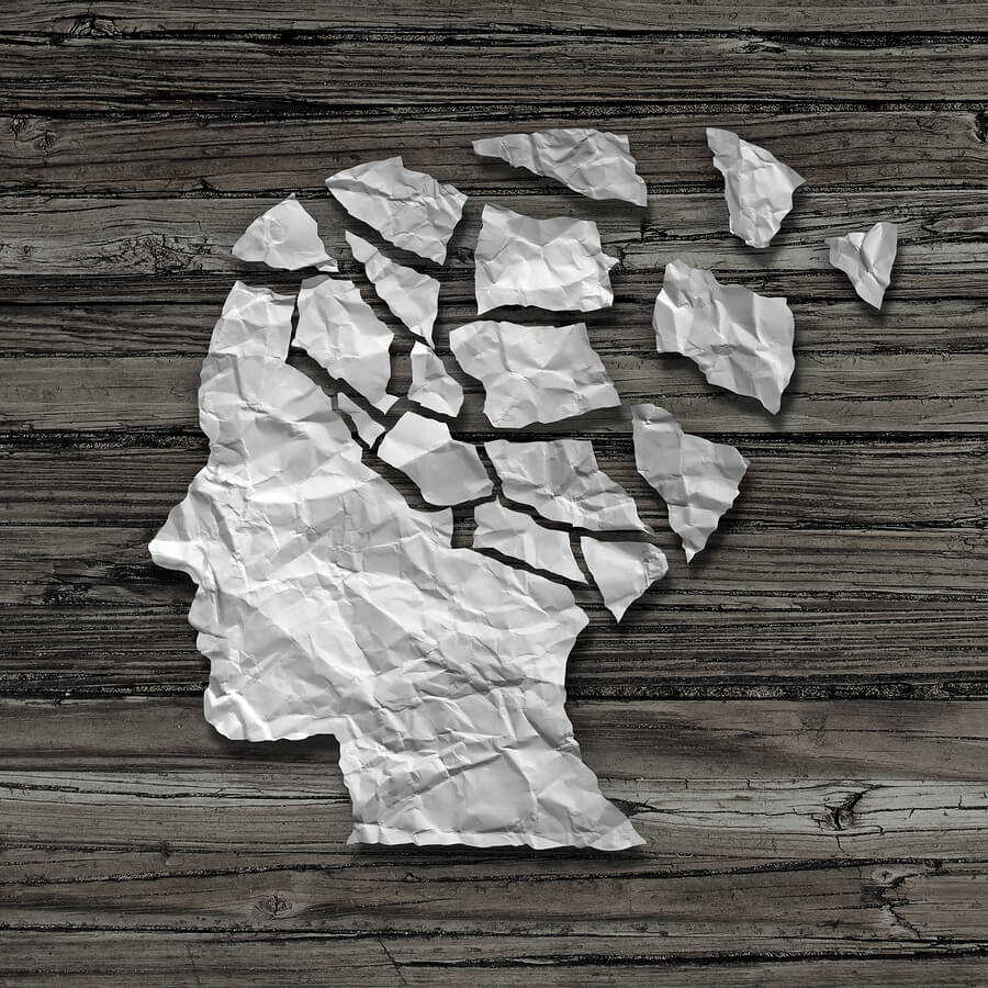 Alzheimer patient medical mental health care concept as a sheet of torn crumpled white paper shaped as a side profile of a human face on an old grungy wood background as a symbol for neurology and dementia issues or memory loss.