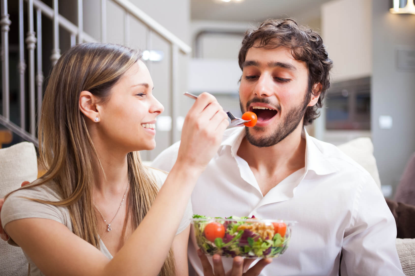 Couple eating a salad in the living room